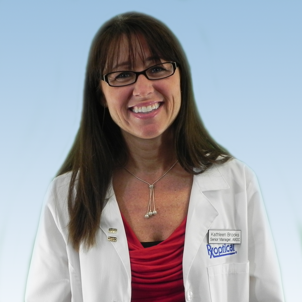 Female Optician with brown hair wearing lab coat and smiling
