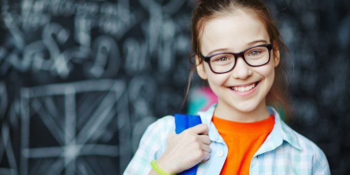 A photo of a girl wearing glasses and her school bag.
