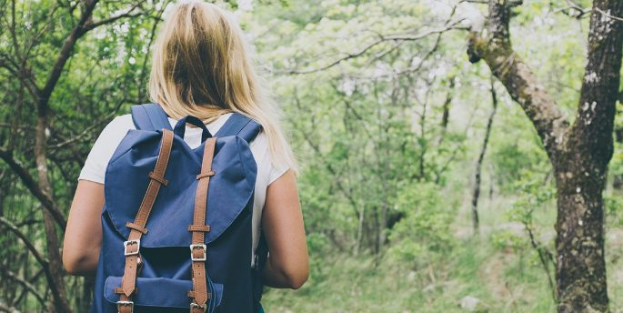 An image of a girl wearing a backpack, hiking in the woods.