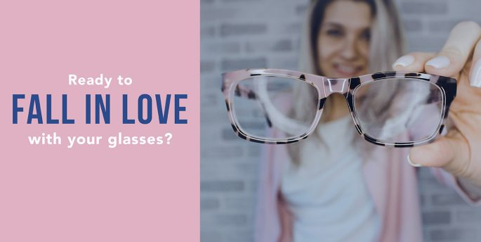 "A woman wearing pink holds up pink tortoise shell glasses while text next to her reads, ""Ready to fall in love with your glasses?"""