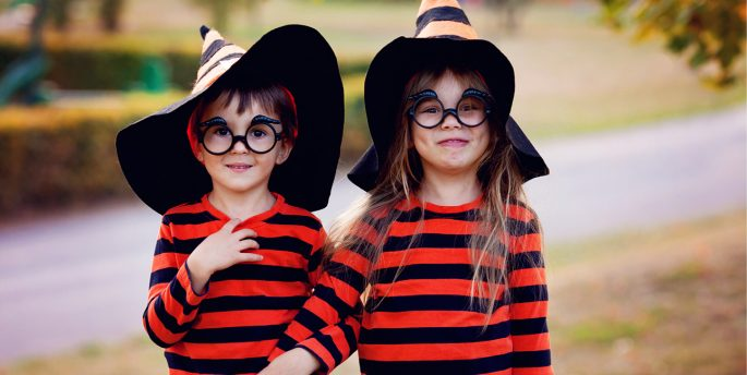 Two children dressed up, with eyeglasses as part of their costume, for Halloween.