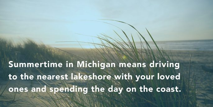 "Grass grows out of the dunes by Lake Michigan while font over them reads, ""SUmmertime in Michigan means driving to the nearest lakeshore with your loved ones and spending the day on the coast."""