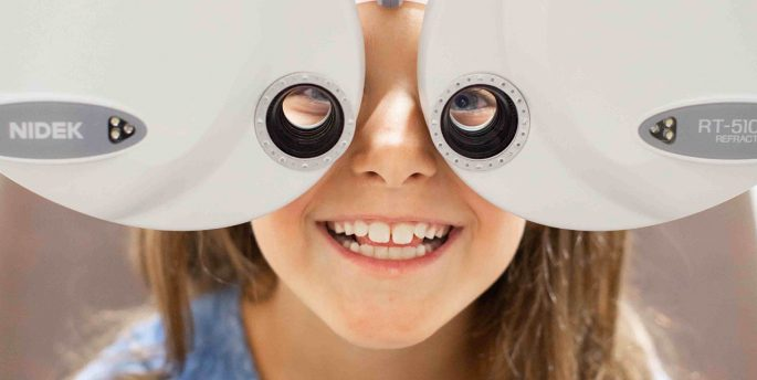 A picture of a young girl taking an eye test.
